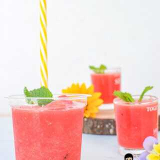 Three cups of watermelon slushie topped with mint leaves with straw for drinking