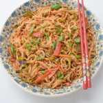 A bowl of veg chow mein with chopsticks